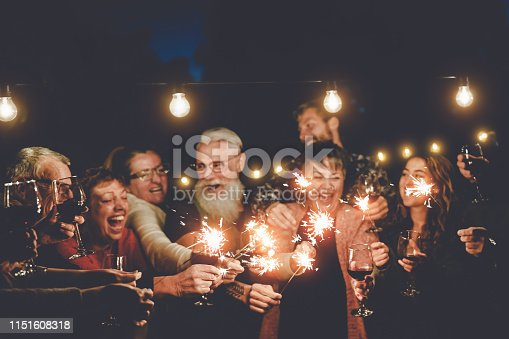 istock Happy family having at dinner party outdoor - Group of multiracial older and young people celebrating together drinking wine holding fireworks sparklers - Concept of youth and elderly parenthood 1151608318