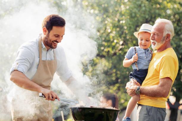 szczęśliwa rodzina o grillu w letnim ogrodzie - grillowany zdjęcia i obrazy z banku zdjęć