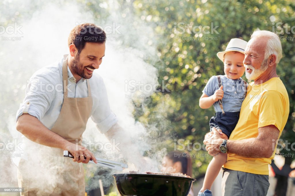 Happy family having barbecue party at summer garden stock photo