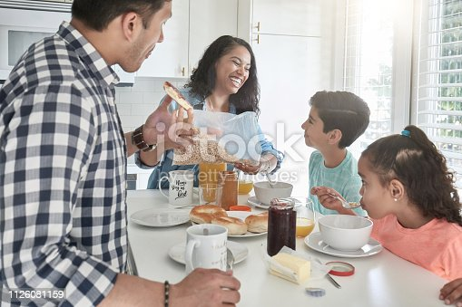 istock Happy family having breakfast in kitchen at home 1126081159