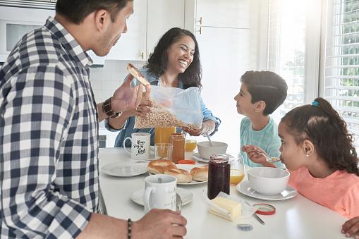 istock Happy family having breakfast in kitchen at home 1126081159