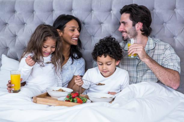 Happy family having breakfast on bed stock photo