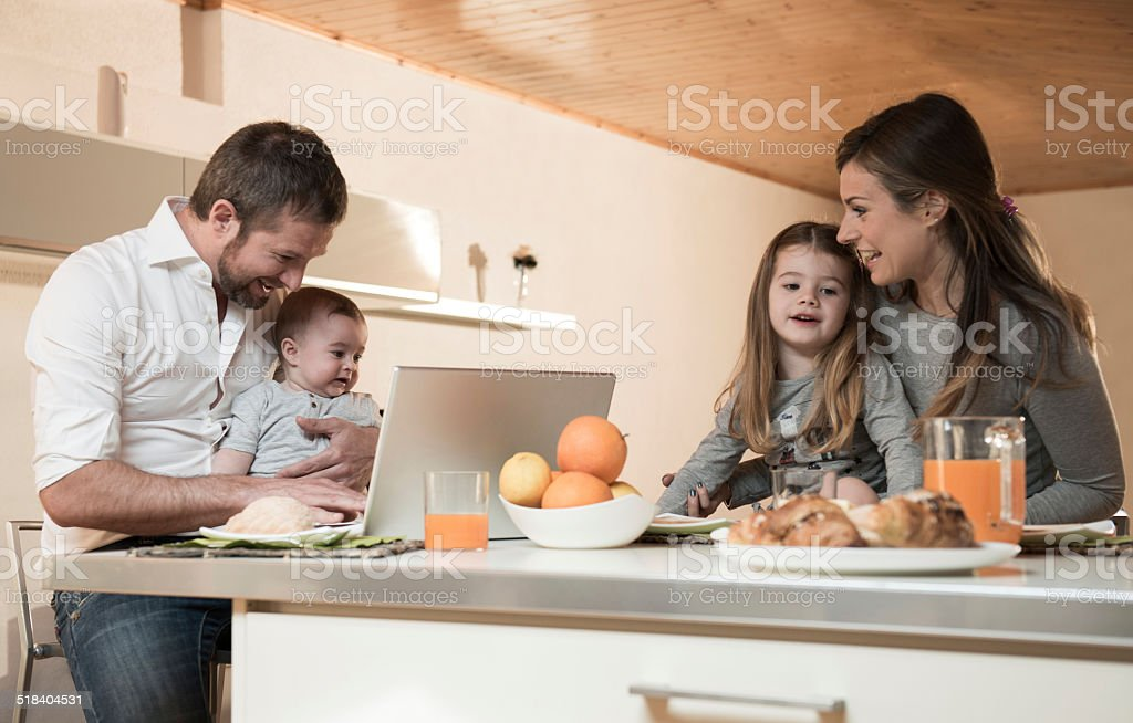 Happy Family Having Breakfast Happy family having breakfast , father on laptop with baby 30-39 Years Stock Photo