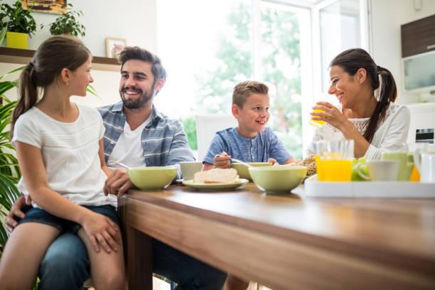 Glückliche Familie mit Frühstück  – Foto