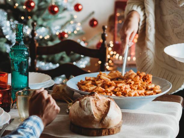 glückliche familie, die dem gemeinsamen weihnachtsmittagessen - italienischer weihnachten stock-fotos und bilder