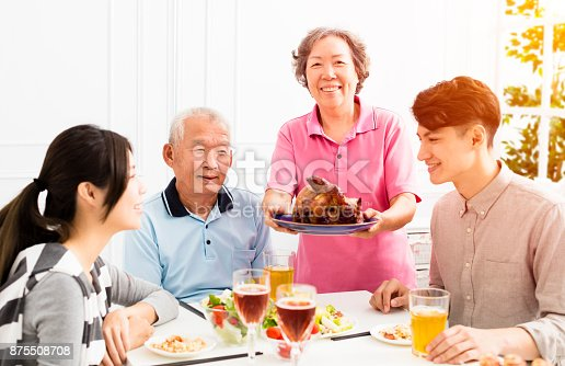 istock Happy family having dinner together 875508708