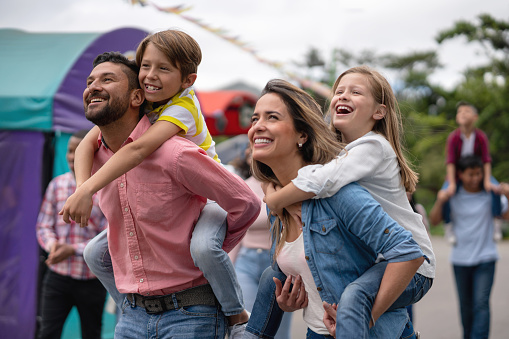 Portrait of a happy family having fun at an amusement park and carrying kids on a piggyback ride - lifestyle concepts