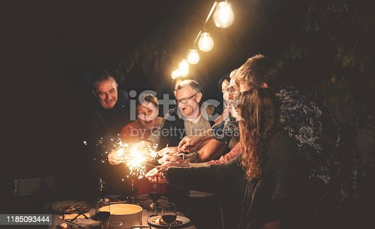 istock Happy family having fun at dinner night party outdoor - Group of people mixed ages celebrating together with fireworks sparklers outside - Holidays culture and parenthood lifestyle concept 1185093444