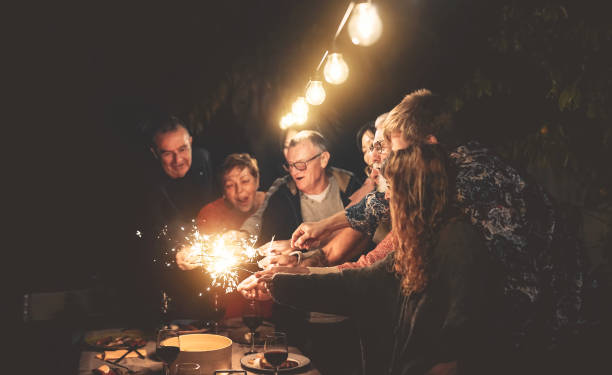happy family having fun at dinner night party outdoor - group of people mixed ages celebrating together with fireworks sparklers outside - holidays culture and parenthood lifestyle concept - vacations food stock pictures, royalty-free photos & images