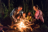 Happy family having fun camping and eating marshmallows by a bonfire – lifestyle concepts