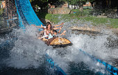 Happy Latin American family having fun and getting wet in a water ride at an amusement park - lifestyle concepts