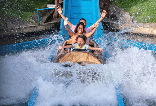 Happy family having fun in an amusement park riding on a fun water ride - lifestyle concepts