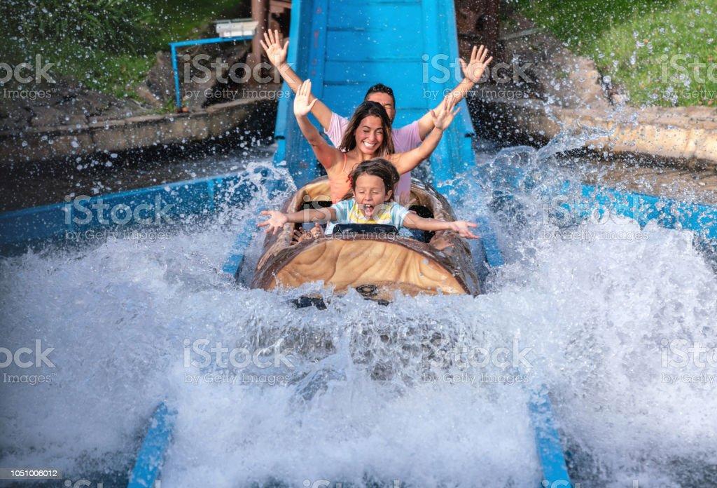 Happy family having fun in an amusement park stock photo