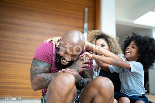 670900812 istock photo Happy family having fun in front of their house 1182268297