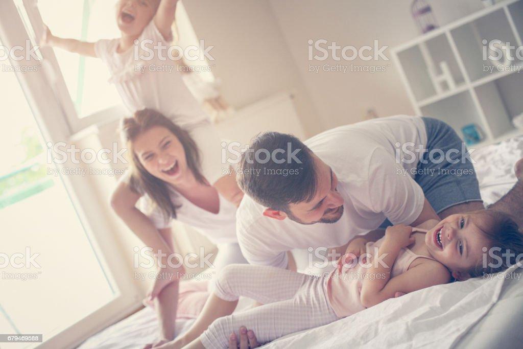 Happy family having fun on bed. royalty-free stock photo