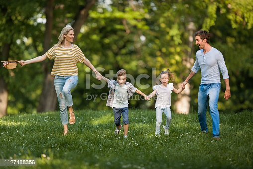 istock Happy family having fun while running in the park. 1127488356
