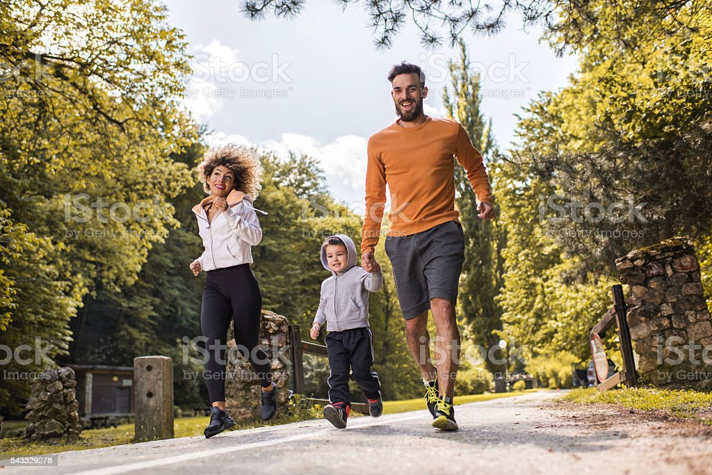 Happy family having fun while running in the park. stock photo