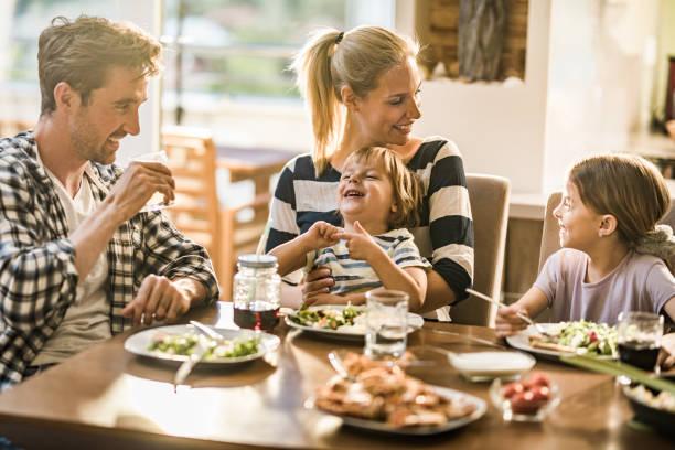 gelukkige familie plezier tijdens een gesprek tijdens de lunchtijd bij de eettafel. - avondmaaltijd stockfoto's en -beelden