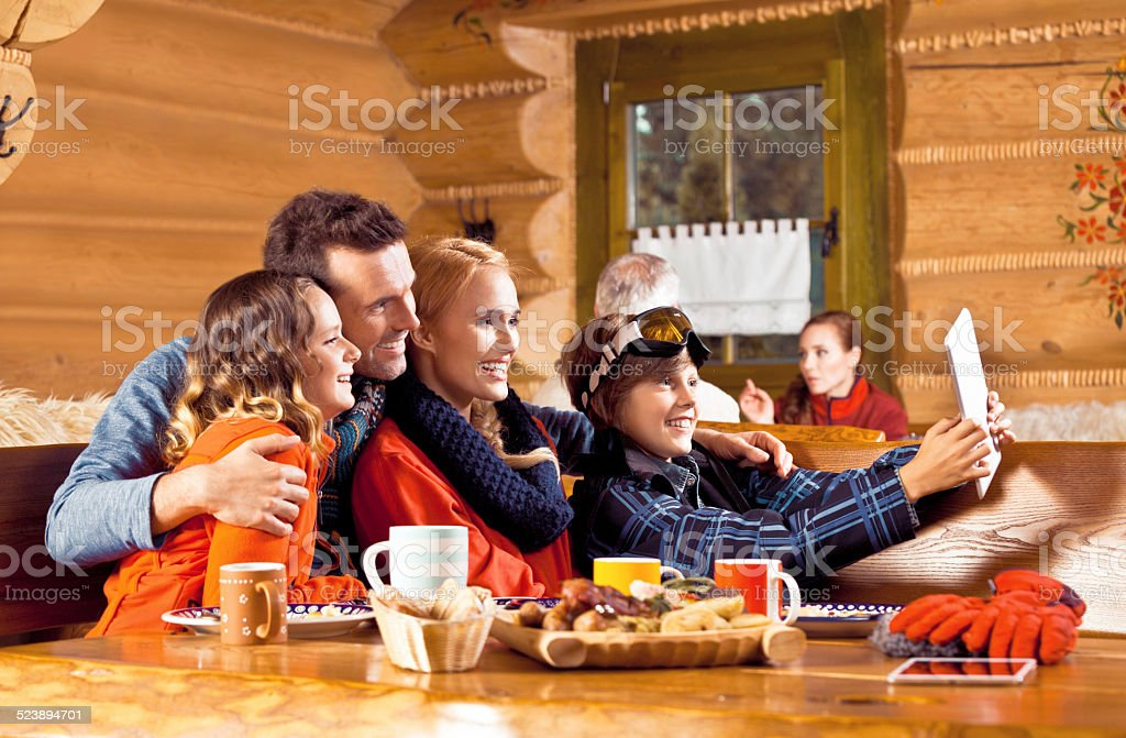 Happy family having lunch after skiing, taking selfie Mother, father and their children wearing winter clothes sitting in a mountain restaurant after skiing, having lunch and taking selfie with a digital tablet. Adolescence Stock Photo