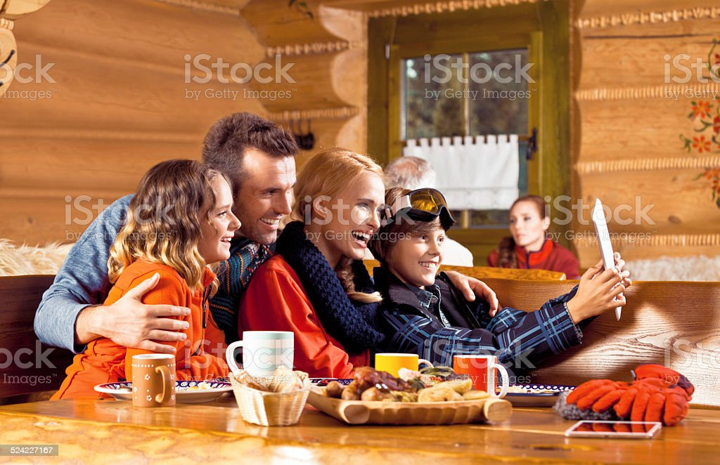 Happy family having lunch after skiing, using digital tablet Mother, father and their children wearing winter clothes sitting in a mountain restaurant after skiing, having lunch and using a digital tablet. Adolescence Stock Photo