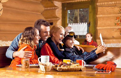 Happy Family Having Lunch After Skiing Using Digital Tablet Stock Photo - Download Image Now