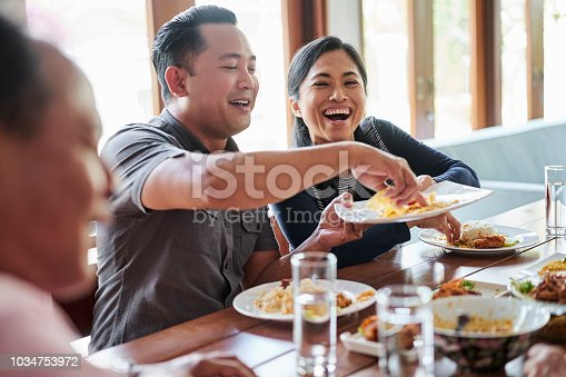 Happy woman passing plate to man while having food at table. Family is having lunch together at home. They are in dining room.