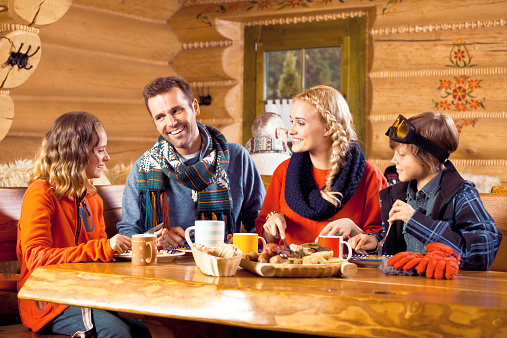 Happy Family Having Lunch In Restaurant After Skiing Stock Photo - Download Image Now