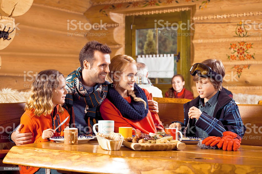 Happy family having lunch in restaurant after skiing Mother, father and their children wearing winter clothes sitting in a mountain restaurant after skiing, talking and enjoying dinner. Adolescence Stock Photo