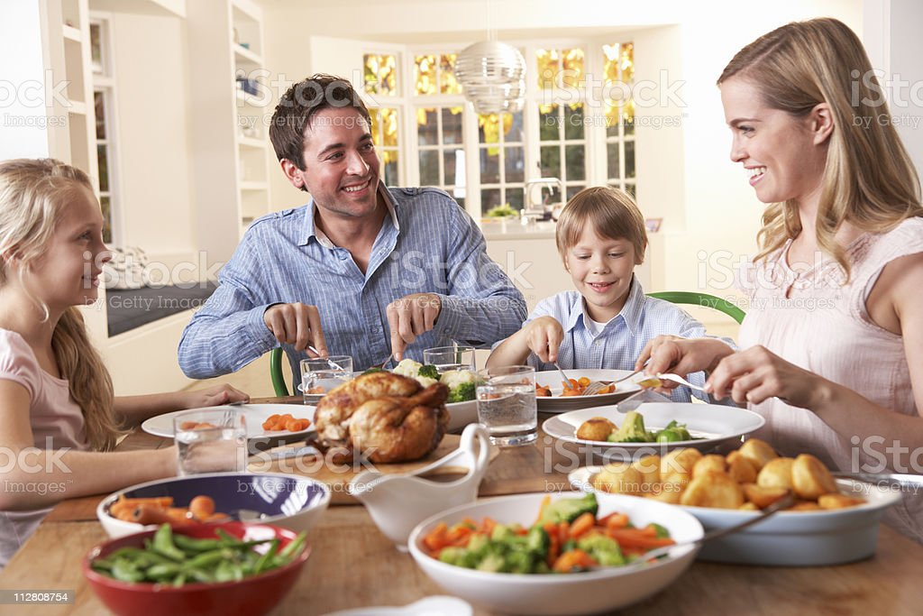 Happy family having roast chicken dinner at table stock photo