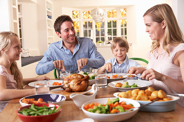 happy family having roast chicken dinner at table - gebraden vlees stockfoto's en -beelden