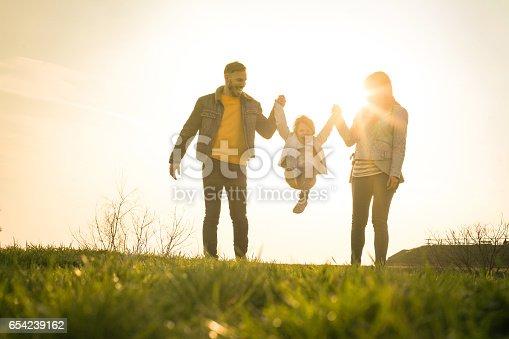 658444674istockphoto Happy family heaving fun in the park. 654239162
