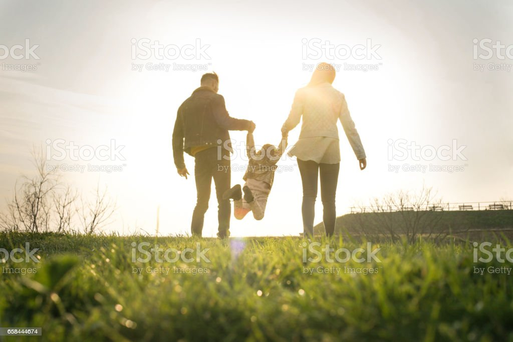 Happy family heaving fun in the park. Happy parents playing with their daughter in the park. Space for copy. From behind. Adult Stock Photo