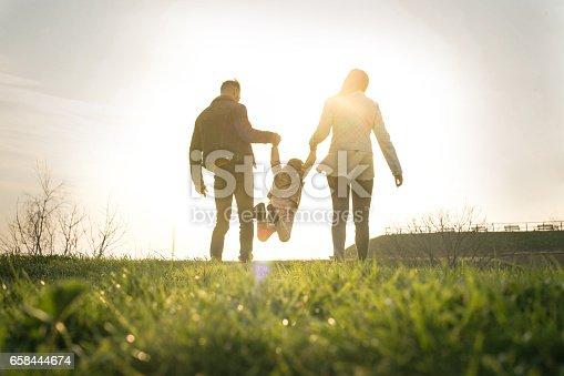 658444674istockphoto Happy family heaving fun in the park. 658444674