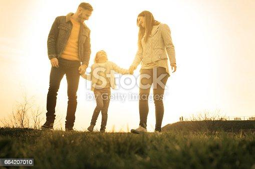 658444674istockphoto Happy family heaving fun in the park. 664207010