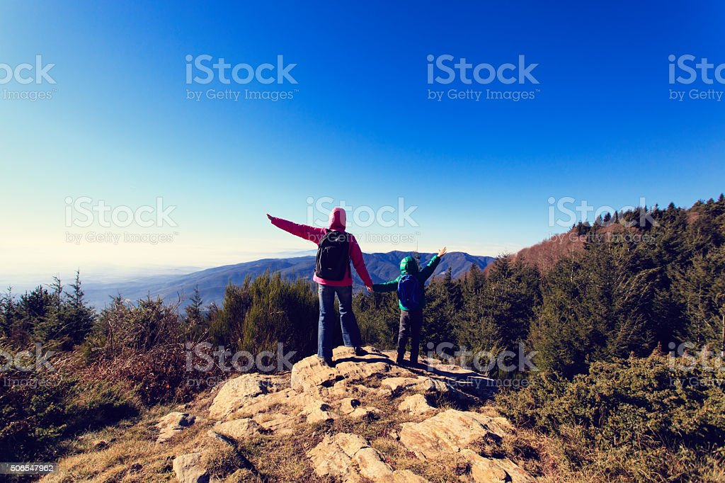 happy family hiking in scenic mountains stock photo