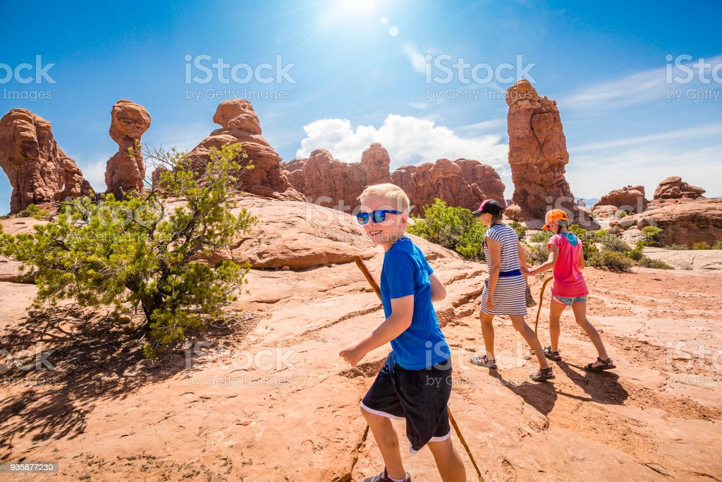 Happy family hiking together in the beautiful rock formations of Arches National Park stock photo