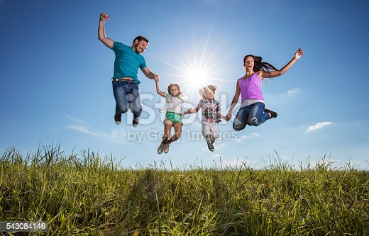 Playful family having fun in nature and jumping high up against the sky. Copy space.