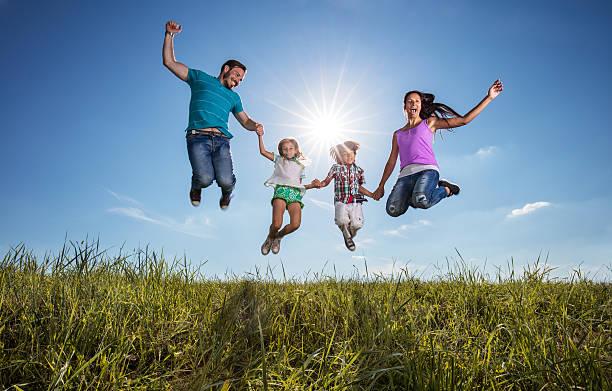 feliz família segurando as mãos e saltar contra o céu. - mãe criança brincar relva efeito de refração de luz imagens e fotografias de stock