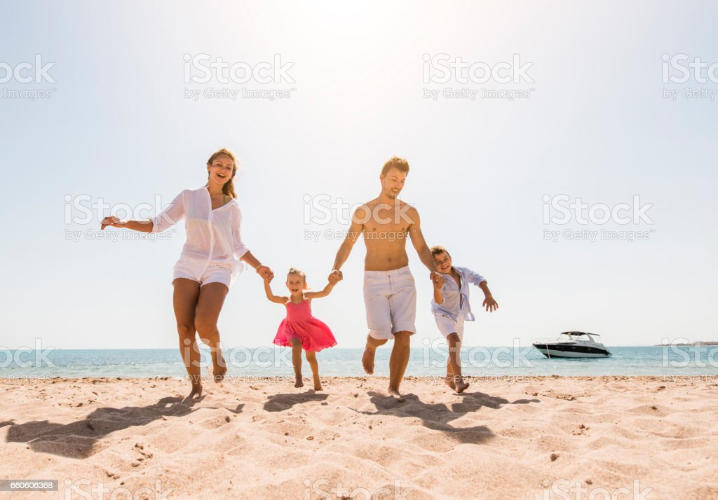 Happy family holding hands and running together on the beach. royalty-free stock photo