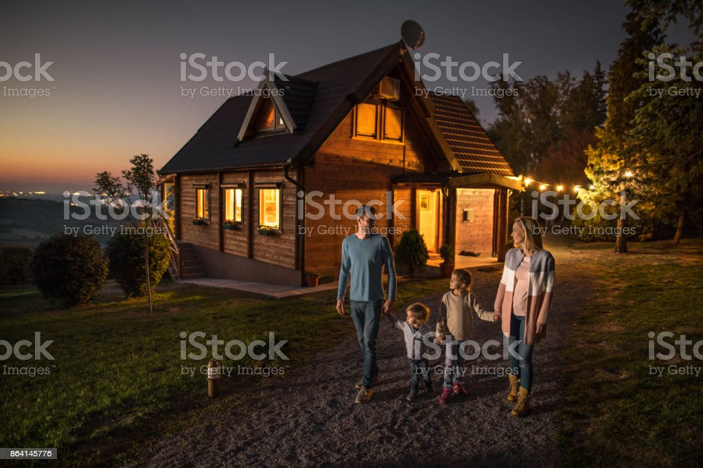 Happy family holding hands and walking by their chalet in the evening. stock photo