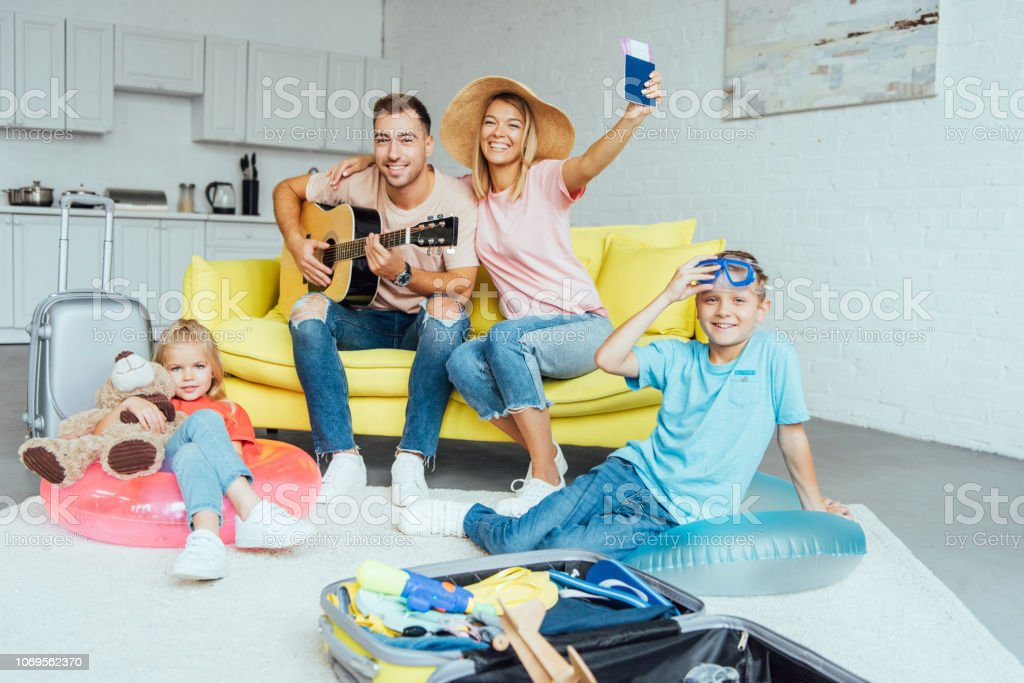 happy family holding passport, packing baggage for summer vacation and having great time, travel concept stock photo