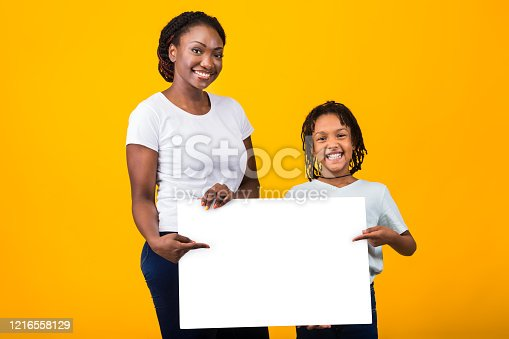 1159989540 istock photo Happy family holding white placard at yellow studio 1216558129