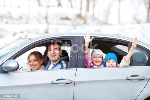 istock A happy family in a car against a snowy backdrop 184378287