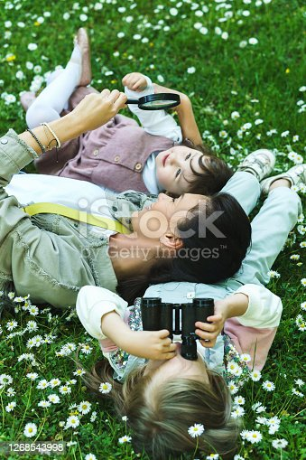 Happy family in a park. Mother and her two daughter lying in chamomile field.