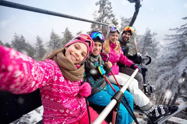Happy family in cable car climb to ski terrain stock photo