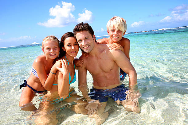 Happy family in crystal clear water stock photo