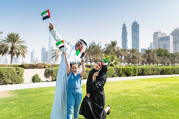 happy family in dubai for the national day - uae flag stok fotoğraflar ve resimler