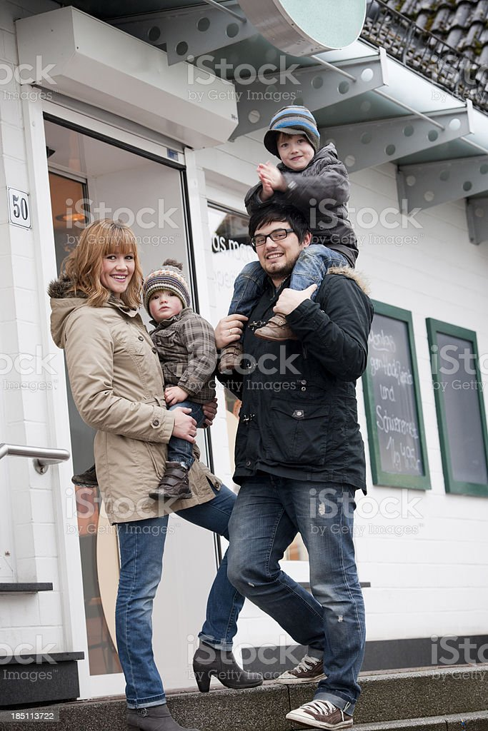 Happy family in front of shop royalty-free stock photo