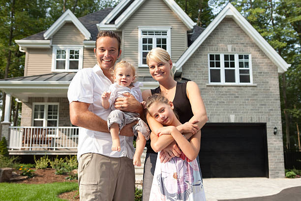 Happy Family In Front Of Their New House stock photo