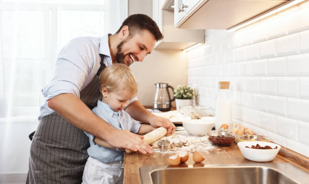 happy family in kitchen. father and child baking cookies - kids cooking stock photos and pictures